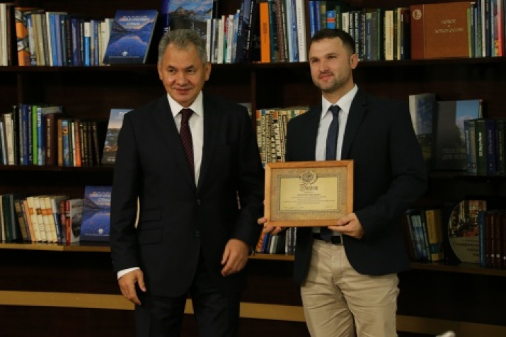 The President of the Russian Geographical Society Sergey Shoygu is handing in the diploma to Egor Ivanov, the winner of the contest in the nomination «For success in public activity». Photo by the press-service of the Russian Geographical Society