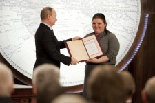 The Chairman of the Board of Trustees of the Russian Geographical Society, The President of Russia, Vladimir Putin is handing in the grant of the Russian Geographical Society to the participant of the Summer School Tatyana Oberukhtina