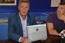 Михаил Малахов демонстрирует памятную табличку, которую планируется установить на горе Юнона