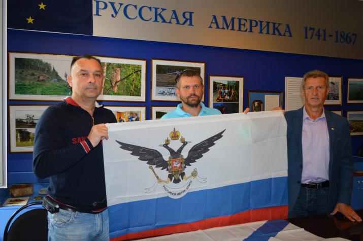 Михаил Малахов (справа) и Александр Бреев (в центре) передают директору Рязанского музея путешественников Александру Капитанову флаг Российско-американской компании, побывавший в экспедиции