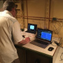 """Fig. 12. Magnetometric laboratory with the MVC-2 stationary recording magnetometers complex on the oceanographic research vessel """"Admiral Vladimirsky"""". IZMIRAN Employee, Soldatov V.A., is monitoring the equipment operation and taking measurements on exper"""